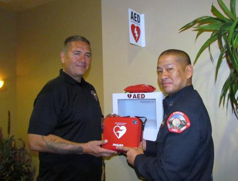 Soboba Tribal Administrator Michael Castello, left, accepts the first AED from Fire Capt. Roger Salmo at the administration building on March 29