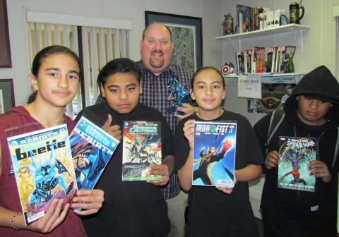 Noli Indian School Principal Donovan Post with a few members of the Comic Book Club showing off some of their favorite titles. From left, Frank Moreno, Xavier Hernandez, Carmel Valenzuella IV and Max Hernandez
