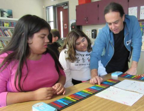 Music teacher Billy Tsounis teaches West Valley High School students Isabella Villegas and Melody Bernal how to play a tune on a hand roll keyboard during a recent Count on Art class