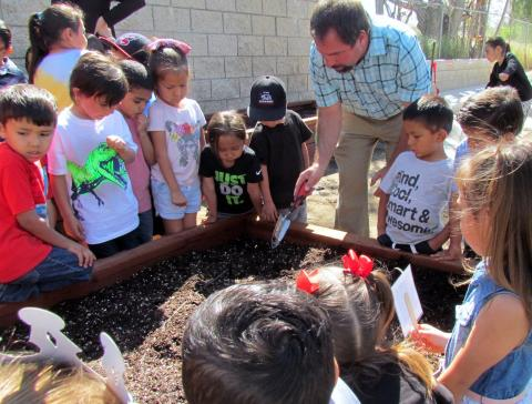 Noli Indian School science and agriculture teacher, Jay Dagostino, shows Soboba Tribal Preschool students how to plant seeds in their new raised bed garden on April 17