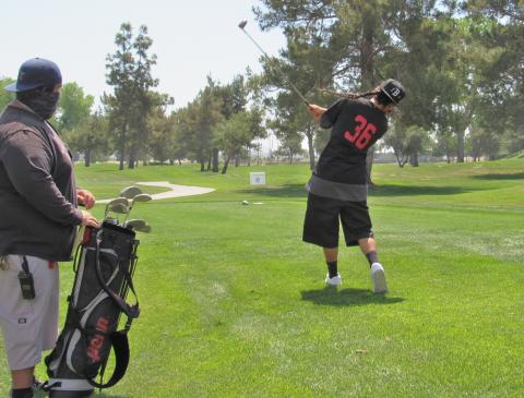 Team Soboba's Jeremiah Ramos takes a swing while Assistant Coach Mike Durrett watches during the Inter Tribal Sports day at Soboba Springs Golf Course on April 17