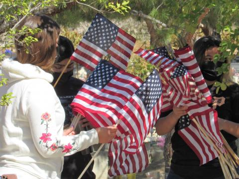 Soboba Youth Council members Tatiana Briones, Iyana Briones and Ciara Ramos carry flags to veterans' gravesites at the Soboba Cemetery ahead of a Memorial Day ceremony there