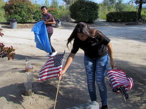 Ciara Ramos places a flag on a veteran's grave as Iyana Briones carries more during a pre-Memorial Day event at the Soboba Cemetery