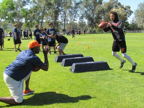 Nick Ferguson tosses a football to San Jacinto's Keith Hunter, 13, during an NFL Play Football skills clinic at the Soboba Reservation on April 1