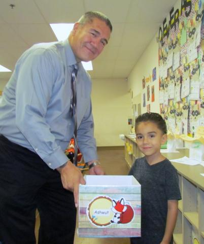 Kindergartner Ashwut Castello shares classwork items with his grandfather, Michael Castello, during Soboba Tribal Preschool's Back-to-School Night on Sept. 12