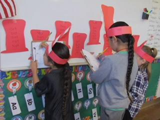 Kindergartners find rhyming words posted on red hats during a Dr. Seuss celebration at Soboba Tribal Preschool