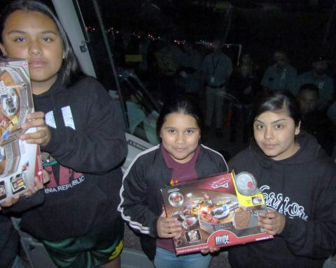 "Soboba Tribal Youths help ""Unstuff the Bus"" of toys at the annual event of toy delivery to the San Jacinto Unified School District's warehouse. From left, Su'la Arviso, Moyla Arviso and Tot Briones. About 200 community members waiting outside the bus to pass the toys along to reach the festively decorated warehouse on Nov. 26 can be seen through the bus' windshield"
