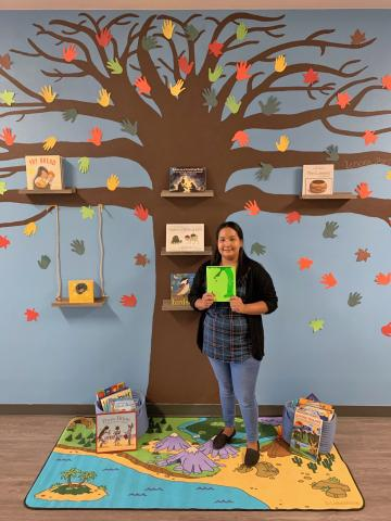 """Lenora """"Ponie"""" Mojado stands in front of the tree she painted on the wall of the Soboba Tribal Preschool's hallway. Shelves on the branches and swing hold books that have a Native American theme and she is holding one of her favorite storybooks: The Giving Tree by Shel Silverstein"""