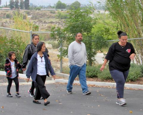 Kelli Hurtado, at right, leads a walking group during a recent Let's Get Moving Mondays program session